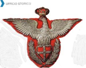 Raro fregio del Corpo per ufficiale. Nel 1925 lo scudo è stato posto sul petto del rapace mentre le fronde di alloro che lo circondano sugli artigli dello stesso.